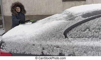 Woman using brush near car in snowfall
