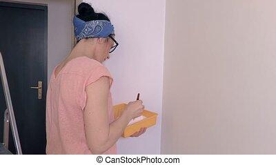 Woman using brush near corner of wall