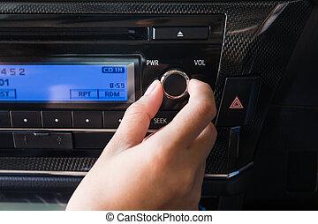 Woman using car volume audio control.