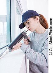 Woman using caulking gun
