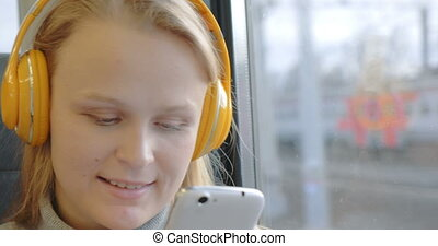 Woman using cell and listening to music in the train