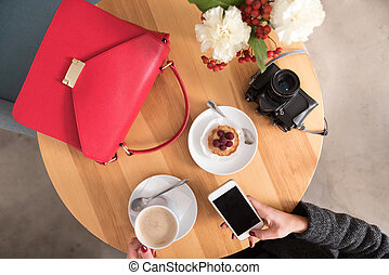 Woman using cell phone and drinking coffee.