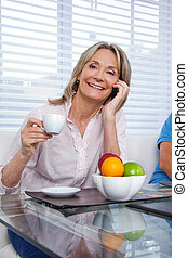 Woman Using Cell Phone at Breakfast Table