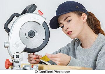 Woman using circular saw reading safety label