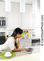 Woman using computer in kitchen - Smiling black woman using ...
