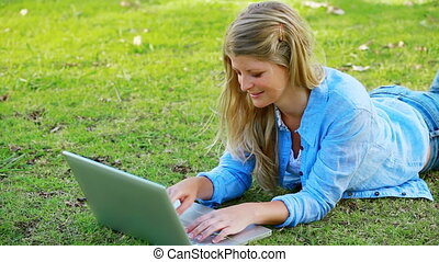 Woman using computer while lying on front in a park