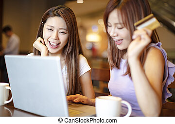 woman using credit card and laptop for online shopping