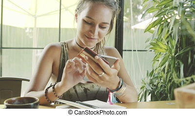 Woman using credit card shopping online with smartphone in cafe