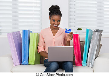Woman Using Debit Card For Shopping On Laptop - Young...