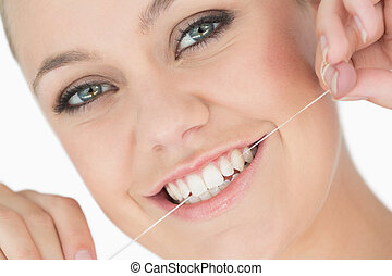 Woman using dental floss in the white background