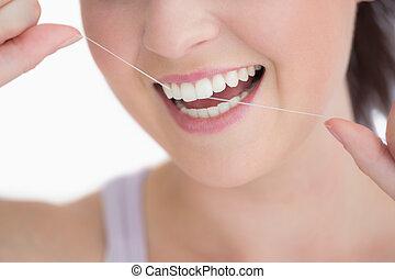 Woman using dental floss against white background