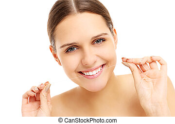 Woman using dental floss - A picture of a young woman using...