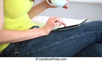 Woman using digital tablet and holding a cup of coffee