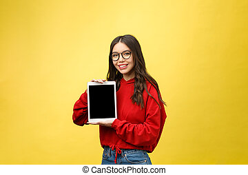 Woman using digital tablet computer PC isolated on yellow background