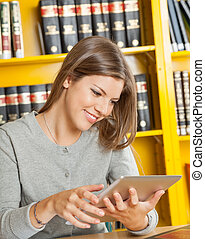 Woman Using Digital Tablet In College Library