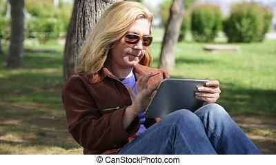 Woman using digital tablet in park