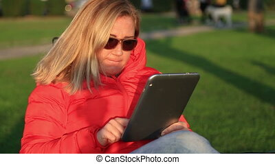 Woman using digital tablet in the city park