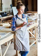 Woman Using Digital Tablet in Woodworks Shop - Portrait of...