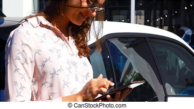Woman using digital tablet while charging electric car 4k