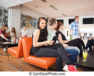 Woman Using Digital Tablet With Friends