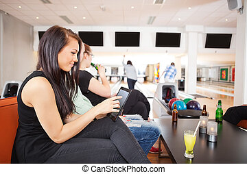 Woman Using Digital Tablet With Friends Bowling in Background