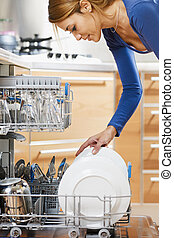 woman using dishwasher - side view of young woman in kitchen...