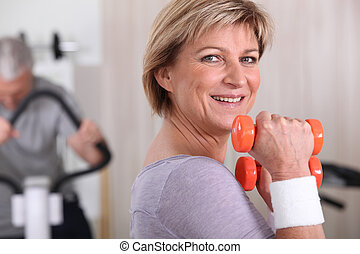 Woman using dumbbells in a gym