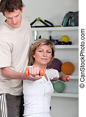 Woman using dumbbells with a personal trainer
