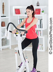Woman using exercise machine at home