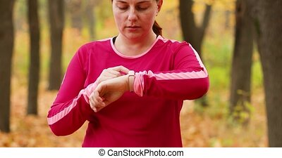 Woman using fitness tracker on wrist on the street in the city park. Golden season maple leaves fallen carpet on the ground. Autumn park