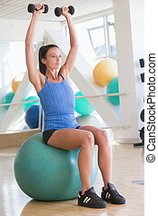 Woman Using Hand Weights On Swiss Ball At Gym