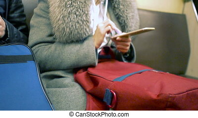 Woman using her cell phone in metro, message, sms, e-mail