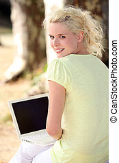 Woman using her laptop in the woods