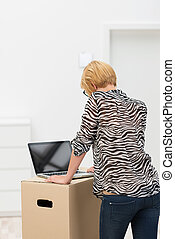 Woman using her laptop on a cardboard box