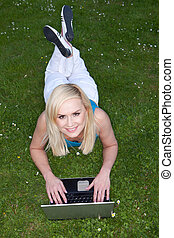 Woman using her laptop on the grass