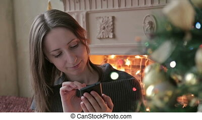 Woman using her mobile phone at christmas at home in the living room
