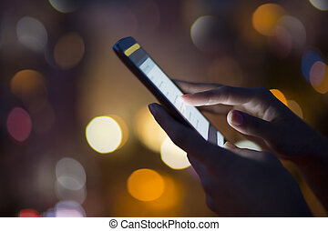 Woman using her mobile phone, city skyline night light background
