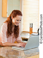Woman using her notebook in the kitchen