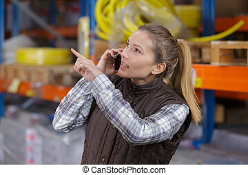 woman using her phone in distribution warehouse