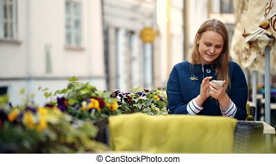 Woman using her smartphone sitting in outdoor cafe