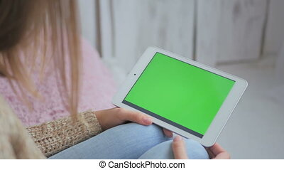 Woman using horizontal tablet computer with green screen