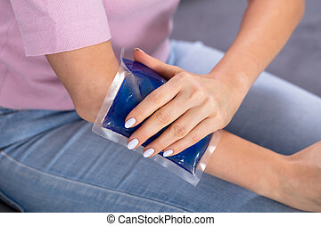 Woman Using Ice Gel Pack On Arm