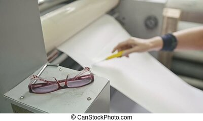 Woman using in printing machine, polygraph industry, front view, glasses in the foreground