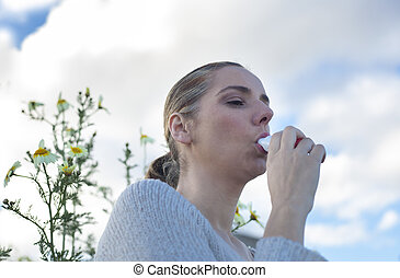 Woman using inhaler to treat asthma allergic