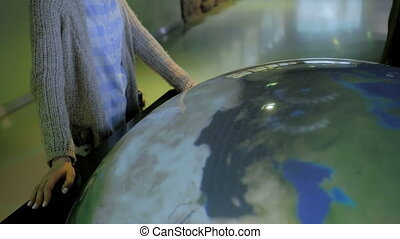 Woman using interactive model of Earth at museum