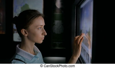 Woman using interactive touchscreen display at modern history museum