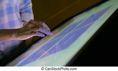 Woman using interactive touchscreen display at modern museum