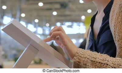 Woman using interactive touchscreen display at urban...