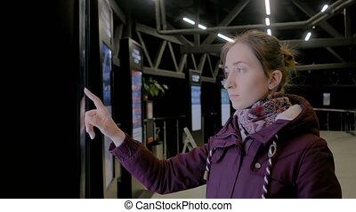 Woman using interactive touchscreen display of electronic multimedia kiosk
