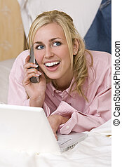 Woman Using Laptop and Cell Phone